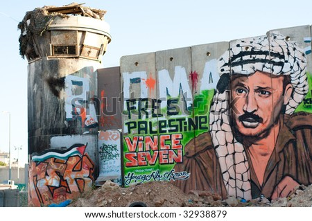 KALANDIA, OCCUPIED PALESTINE - MAY 28, 2009: The Israeli separation wall, covered with graffiti including a portrait of a young Yasser Arafat, divides Palestinian lands in the West Bank on May 28, 2009