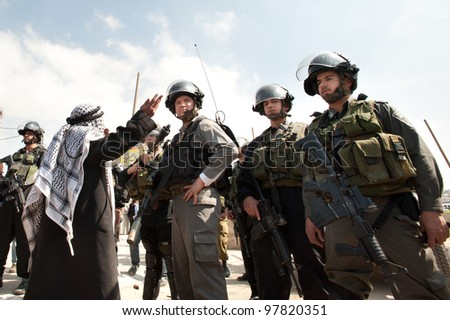 KALANDIA, OCCUPIED PALESTINIAN TERRITORIES - MARCH 8: A Palestinian man confronts Israeli soldiers at Kalandia checkpoint during demonstrations on March 8, 2012.