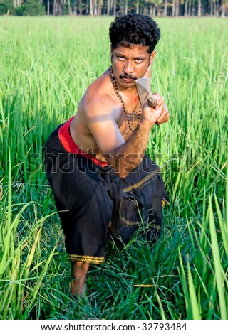 Kalarippayat, warrior with spear in deep green rice paddy, indian ancient martial art of Kerala, India - stock photo