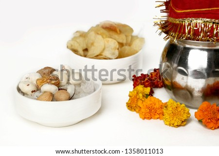 Kalash with coconut and chunni with floral decoration for navratri pooja. Picture of dry fruit and potato chips in the bowl. Isolated on the white background.