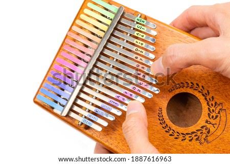 Photo of  Kalimba playing in hands and plucking the tines with thumbs, Kalimba or Mbira is an African musical instrument that has colorful label attached on metal tines isolated on white background