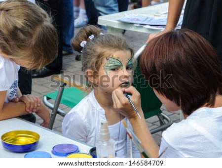 KALININGRAD, RUSSIA - JULY 14: An unidentified child, painting at a girl\'s face on City Day of Kaliningrad celebration on July 14, 2013 in Kaliningrad, Russia