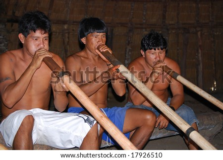 KAMAYURA VILLAGE, BRAZIL - MAY 18: Members of a threatened Indian tribe, the Kamayura, playing sacred flutes on May 18, 2008, in the Kamayura village.