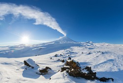 Kamchatka Peninsula, winter mountain landscape, beautiful panoramic view of eruption active volcano in clear sunny weather with blue sky. Klyuchevskoy Volcano, Klyuchevskaya Group of Volcanoes, Russia
