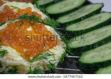 Kanapes with butter and red caviar, and sliced cucumber. Stock fotó ©