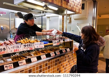 KANAZAWA, JAPAN - MARCH 28 : Unidentified Japanese shopkeeper hands a food package to an unidentified customer at the Omicho Market on March 28, 2012 in Kanazawa, Japan.