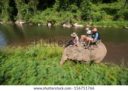 KANCHANABURI, THAILAND, MAY24 : Tourist riding elephant trough jungle and cross river on May 24 2013 in Kanchanaburi, Thailand
