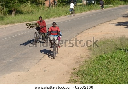 KANDE, MALAWI-APRIL 12:Bundles of sugar cane transported wheeling a bicycle,and a baby transported on the back of a bicycle, in Kande on April 12, 2011.Bicycles are the transport of choice in Malawi.