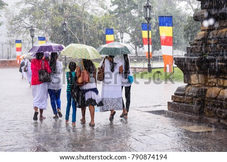 Kandy, Sri Lanka. Sri lankan women and children hiding under umbrellas during heavy monsoon rain at the temple of the tooth in Kandy.