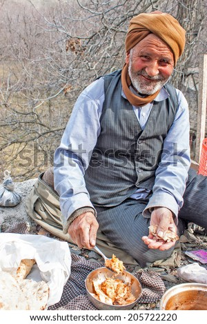 KANG IRAN FEBRUARY 24 Old village man eats his lunch on February 24 2013 in a village Kang Iran Kang is a small stepped village in northern Iran