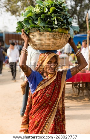 KANHA, INDIA - FEBRUARY 04: A woman carrying produce at local food market on February, 04 in village of Kanha.