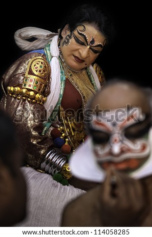 KANNUR - DECEMBER 06: Unidentified Kathakali performers applying face make-up prior to a performance on December 06, 2011 at a small village near Kannur, Kerala, India.