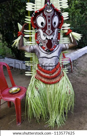 KANNUR - DECEMBER 09: Unidentified Theyyam performer in traditional costume and face mask taking a break during a performance on December 09, 2011 at a small village near Kannur, Kerala, south India.