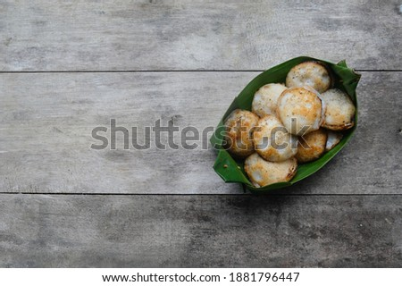 Kanom Krok or Thai coconut pudding contained in banana leaf package on wooden table. Kind of Thai sweetmeat. Mortar-toasted pastry. It made of coconut milk Zdjęcia stock ©