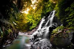 Kanto Lampo Waterfall gianyar bali - Scenic, seasonal waterfall cascading down a stepped rock wall into a shallow wading pool
