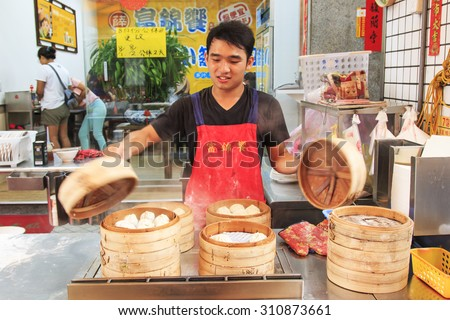 Kaohsiung, Taiwan - August 9,2015: Street food vendor in Kaohsiung, Taiwan, preparing the steamed Xiao Long Bao, a traditional chinese dish invented in Shanghai