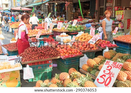 Kaohsiung, Taiwan - June 22,2015: People selling and buying food in a traditional fruit and vegetable market of Taiwan