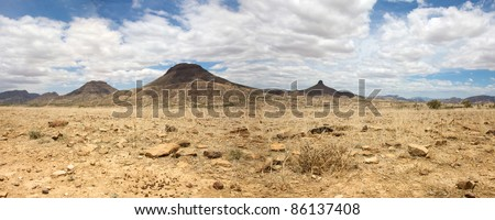 Kaokoland game reserve in Namibia, sand track going toward the Skeleton Coast Desert with a blue sky