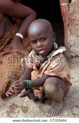 KAOKOLAND, NAMIBIA - MAY 9: An unidentified Himba  child with ethnic decorations sits in front of traditional cabinwatching adults working on May 9 2010, in Himba Village near the Kamanjab Namibia