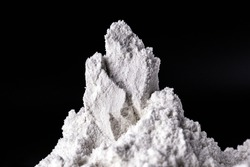 Kaolin on black isolated, powdered background. Kaolin is a mineral of inorganic constitution, chemically inert, extracted from deposits and processed in different granulometric bands