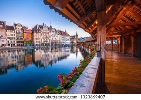 Photo of  Kapellbrucke historic wooden bridge in Luzern and waterfront landmarks dawn view, town in central Switzerland
