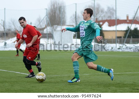 KAPOSVAR, HUNGARY - FEBRUARY 18: Unidentified players in action at a friendly soccer game Kaposvar (green) vs. Dombovar (red) - February 18, 2012 in Kaposvar, Hungary.