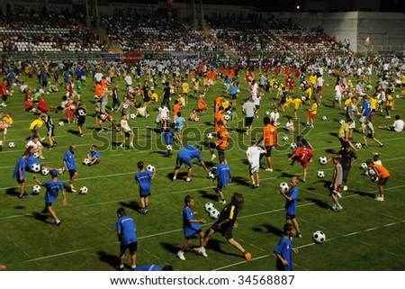 KAPOSVAR, HUNGARY - JULY 23: Many competitors at the Guinness world record breaking attempt (Most people keep the football in the air Juggling together) - July 23, 2009 in Kaposvar, Hungary