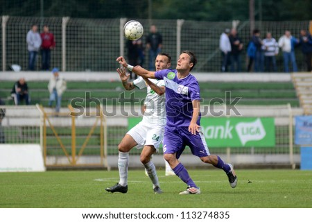 KAPOSVAR, HUNGARY - SEPTEMBER 14: David Hegedus (white 24) in action at a Hungarian National Championship soccer game - Kaposvar (white) vs Ujpest (purple) on September 14, 2012 in Kaposvar, Hungary.