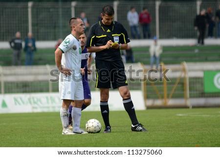 KAPOSVAR, HUNGARY - SEPTEMBER 14: Viktor Kassai (referee) in action at a Hungarian National Championship soccer game - Kaposvar (white) vs Ujpest (purple) on September 14, 2012 in Kaposvar, Hungary.