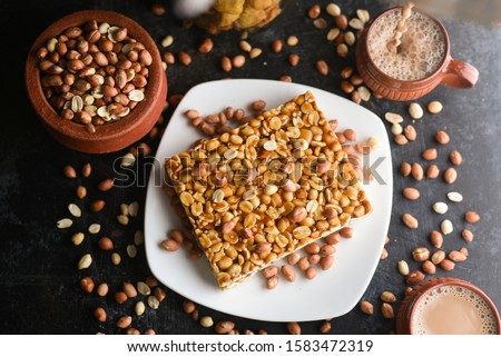Kappalandi Mittayi, Peanut Chikki and milk tea. sweet food tea time snack on dark black background Kerala South India. Popular Indian festival snack groundnut dessert for Onam, Vishu, Diwali, Ramadan.