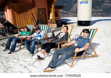KAPRUN AUSTRIA - MARCH 5: Maiskogel Fanlauf 2011. Men relaxing in canvas chair  at charity ski race with many celebrities in austria on March 5, 2011 at the Maiskogel in Kaprun, Austria