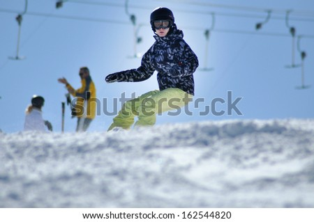 KAPRUN - MARCH 5: Unidentified snowboarder snowboarding down the slope in the Austrian Alps, during the school vacation. On March 5, 2013, in Kitzsteinhorn, Austria - stock photo