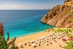Kaputas beach with blue water on the coast of Antalya region in Turkey with sun umbrellas on the beach. Travel destination
