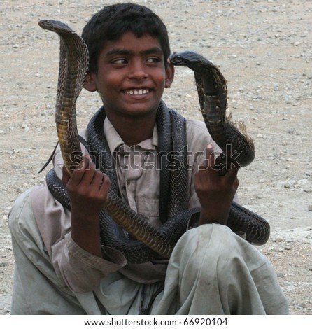 KARACHI, PAKISTAN - August 2: Unidentified snake charmer plays with his cobras on August 2, 2010 in Karachi, Pakistan.