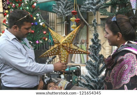 KARACHI, PAKISTAN - DEC 12: A Christian family busy in decorating their home in  connection of Christmas on December 12, 2012 in Karachi.