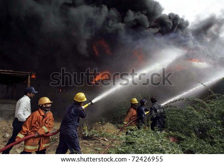 KARACHI, PAKISTAN - MAR 03: Firefighters extinguish fire after fire broke out at a shoe factory at Manghopir area on March 03, 2011in Karachi.