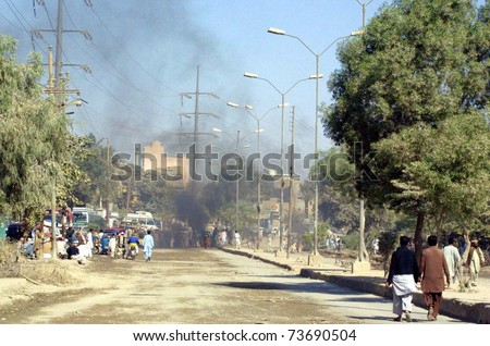 KARACHI, PAKISTAN - MAR 21: Smoke rises at a road as angry mob burn tires as violence erupts in city after incidents of the target-killings in different areas of the city on March 21, 2011 in Karachi.