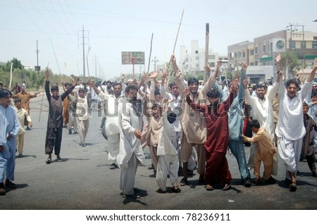 KARACHI, PAKISTAN - MAY 29: Residents of Korangi hold sticks chant slogans against shortage of drinking water and electricity load-shedding in their area during protest on May 29, 2011 in Karachi, Pakistan