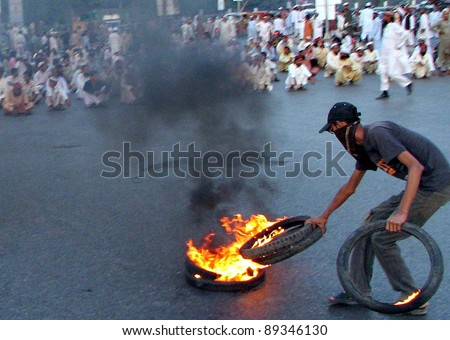 KARACHI, PAKISTAN - NOV 22: An angry protester burns tyres during protest demonstration of Jamat Ahle Sunnat in favor of their demands at MA.Jinnah road on November 22, 2011in Karachi.