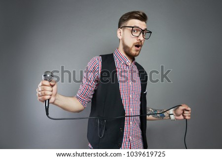 Karaoke man sings the song to microphone, singer with beard on grey background. Funny man in glasses holding a microphone in his hand at the karaoke singer sings the song