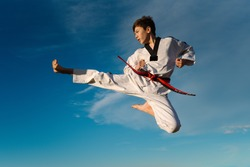 Karate boy kicks in the air and flies over the blue background of the sky. Practicing Taekwondo in nature. Black martial arts belt