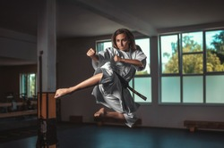 Karate girl with black belt doing in air kick - on belt Kaishin wich means