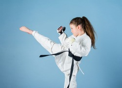 Karate gives feeling of confidence. Strong and confident kid. She is dangerous. Girl little child in white kimono with belt. Karate fighter ready to fight. Karate sport concept. Self defence skills.
