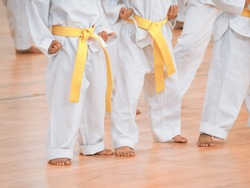 Karate or tae kwon do,martial arts.A closed up shot little kids wearing white kimono with yellow belt in training course.Extreme fight sports. Concepts of becoming a professional fighter