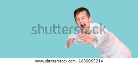 Karate young boy in white uniform makes a hit aggressively shouting o n blue background Stock fotó ©