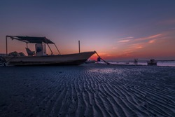Karbabad, Manama, Bahrain : 20th Jan 2020 - Beautiful sunset new of the beach with fishing boats and sand patters