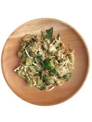 Karedok is Indonesian salad made from mix raw vegetables with peanut sauce dressing. Karedok on a wooden plate isolated on white background. The vegetables are cucumber, beans sprout, long bean, etc