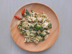 Karedok is Indonesian traditional salad made from raw vegetables with peanut sauce dressing. Karedok and two chilis on wooden plate. The veggies are cucumber, cabbage, basil, beans sprout, long bean