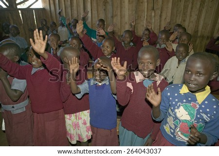 Karimba School with school children raising their hands in classroom in North Kenya, Africa
