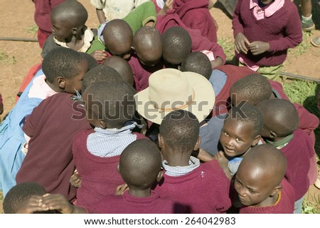 Karimba School with school children surrounding white man with straw hat on, in North Kenya, Africa